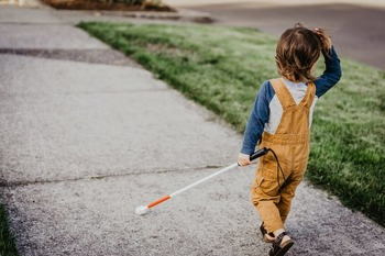 A child walks with a white cane