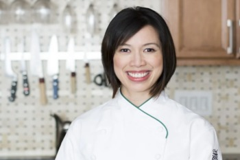 Christine Ha stands in a kitchen wearing a white chef jacket