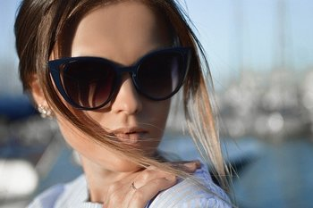 A young woman wearing sunglasses looks away from the camera