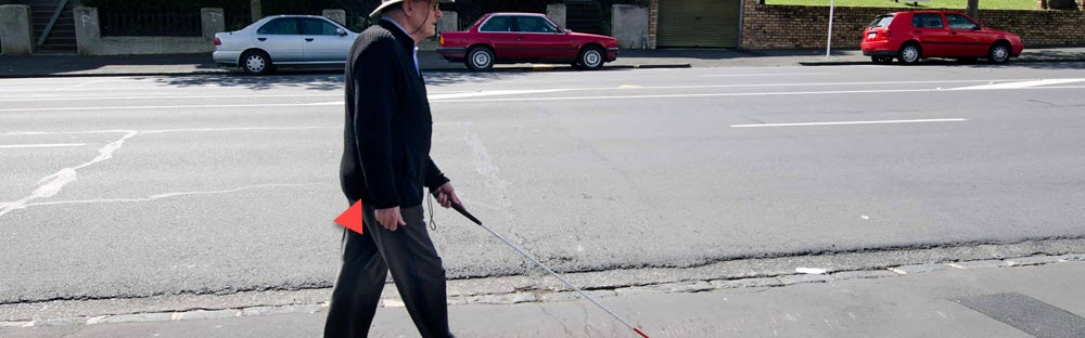 Photo of person that can't see walking down the street with the help of a cane