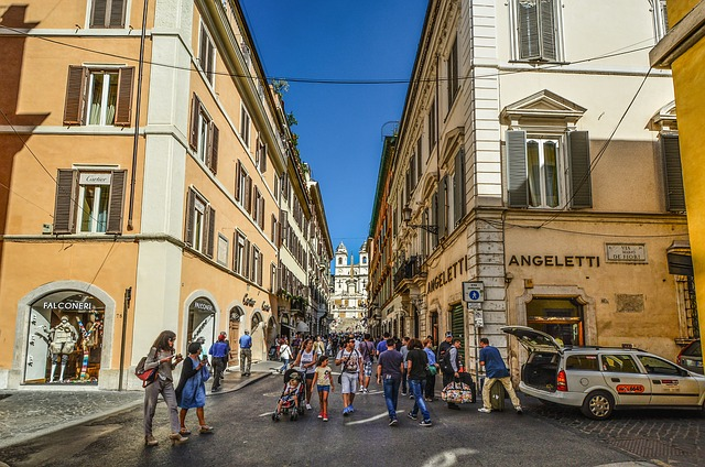 A street view shot of a busy shopping area in Rome with 4 story orange buildings on both sides of a narrow street.
